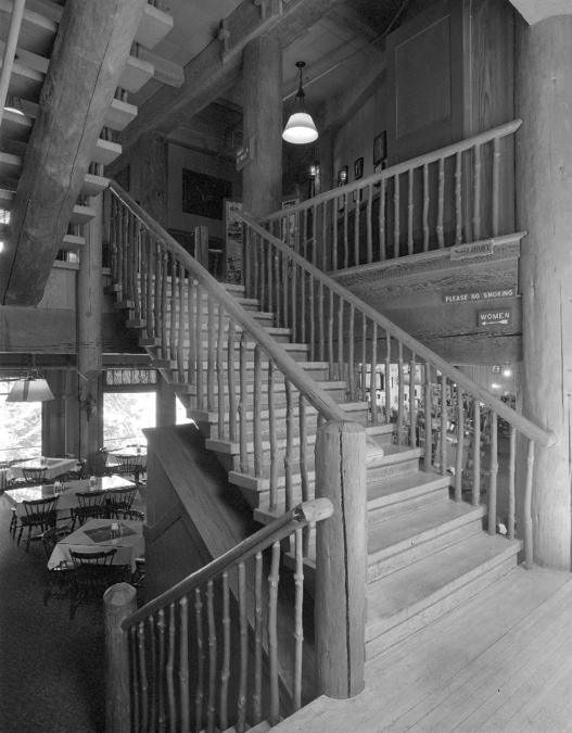 The grand stair as viewed between the third floor dining room and lobby on the fourth floor. Pine logs were used for stringers. The steps are oak and the balustrade is madrone with lodgepole pine railings.